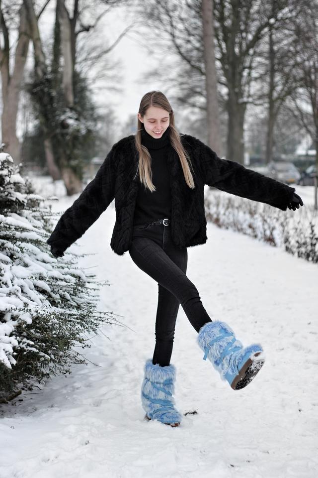 Outfit met blauwe fluffy sneeuwlaarzen snowboots met imitatiebont zwarte winter outfit mode blogger sneeuw inspiratie